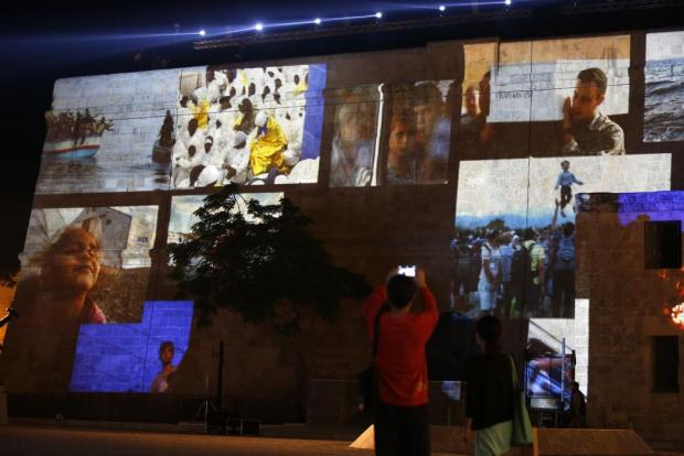 People take pictures of projections showing images of migrants on the facade of St James Cavalier during a rehearsal of the opening ceremony of the 2015 Valletta Summit on Migration in Valletta on November 10. Photo: Darrin Zammit Lupi
