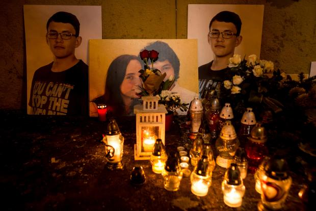 A picture taken in Bratislava on February 20, 2019 shows candles beside portraits of Slovakian journalist Jan Kuciak and his fiancee Martina Kusnirova who were found shot dead at the couple's home near Bratislava.