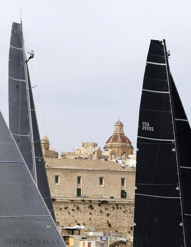 "Crew members climb on the masts of the yachts ""Caro"" (left) of Switzerland and ""Rambler"" (right) of the U.S. as they make their way out of Valletta's Grand Harbour at the start of the annual Rolex Middle Sea Race on October 17. Over 100 yachts from 22 different countries competed in the 608 nautical mile Mediterranean classic, which takes the yachts from Malta, around Sicily and back. Photo: Darrin Zammit Lupi"