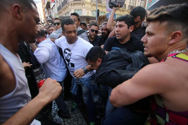People surround the man suspected of having stabbed the candidate. Photo: Reuters
