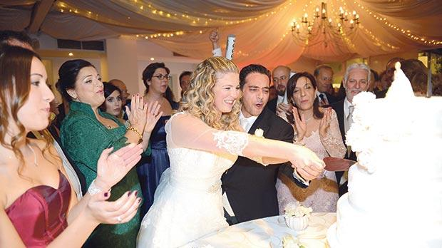 The bride and groom cutting their wedding cake surrounded by guests .Photos: Rene Rossignaud