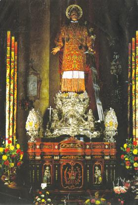The processional statue of St Lawrence dressed in historic vestments. Note the fine craftsmanship and the design of the pedestal and walnut platform.