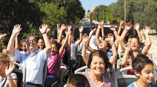 A group of schoolchildren had a double treat yesterday when they were joined by the Prime Minister Lawrence Gonzi and his wife Kate aboard an open-topped double-decker bus for a trip to Valletta and a personal tour of the PM's office at the Auberge de Cas