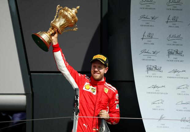 Ferrari driver Sebastian Vettel lifts the trophy at Silverstone.