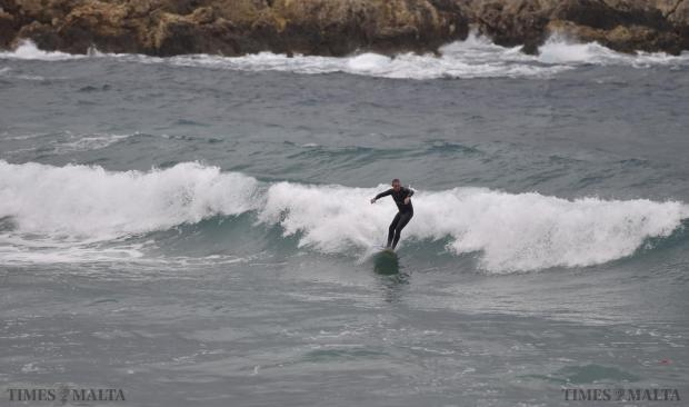 A surfer at Għajn Tuffieħa catches a wave during strong winds that lashed the island on January 16. Photo: Mark Zammit Cordina