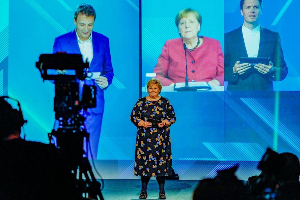La primera ministra de Noruega, Erna Solberg (centro) y la canciller Angela Merkel (en la pantalla al fondo) en la inauguración oficial de NordLink, la primera conexión eléctrica entre Noruega y Alemania.  Foto: Gorm Kallestad / NTB / AFP