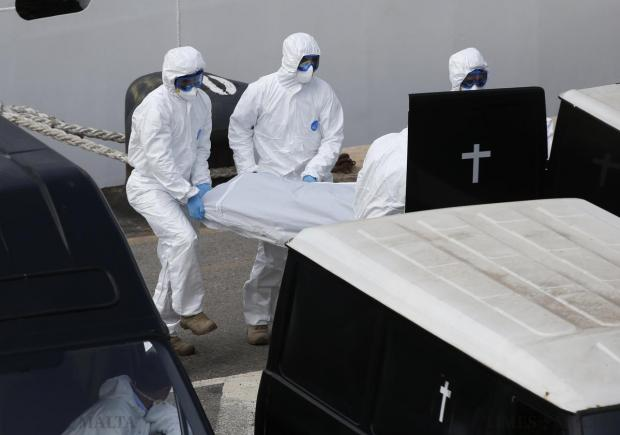 Armed Forces of Malta personnel in protective clothing carry the body of a dead immigrant into a hearse after disembarking from the Italian coastguard ship 'Bruno Gregoretti' in Senglea on April 20. An Italian patrol ship arrived in Malta on Monday with 24 corpses recovered out of hundreds feared drowned after a migrant boat capsized in the Mediterranean, in one of the worst disasters yet in a growing humanitarian crisis. Photo: Darrin Zammit Lupi