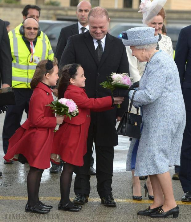 Queen Elizabeth is greeted by Maltese Prime Minister Joseph Muscat and his twin daughters, Etoile Ella and Soleil Sophie, on her arrival in Malta on November 26 for an official state visit. Photo: Matthew Mirabelli
