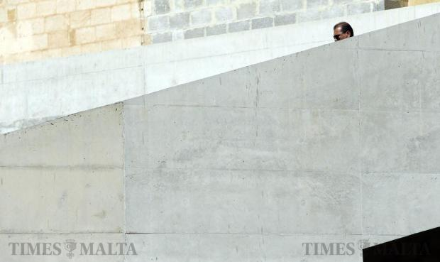 A man is partly hidden behind a wall as he walks down a staircase at Dock One in Cospicua on May 21. Photo: Darrin Zammit Lupi