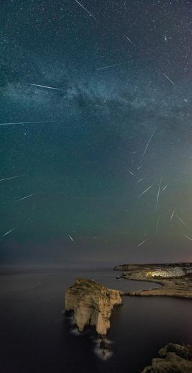 Perseids meteors over Dwejra Bay and Fungus Rock, Gozo. A composite image of 24 meteors captured over a period of 90 minutes on August 14, from the collection Starscapes of Malta, a series of landscape astrophotography images by Gilbert Vancell. http://gvancell.com