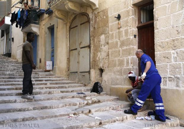 A 19-year-old Sudanese man is tended to by a paramedic after being grievously injured in a fight with a Libyan man in Valletta on June 4. The Sudanese man was pushed through the glass door of a hotel and rushed to hospital with serious head wounds. Photo: Darrin Zammit Lupi