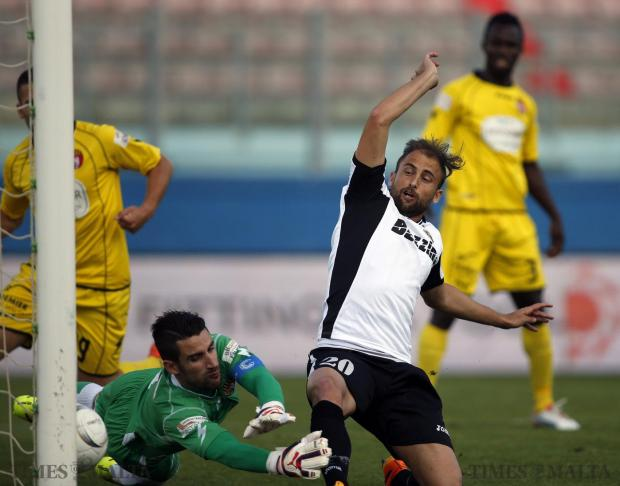 Hibernians defender Andrei Agius (right) flicks the ball past Qormi goalkeeper Matthew Farrugia to score a goal during their FA Trophy semi-final football match at the National Stadium in Ta' Qali on May 17. Photo: Darrin Zammit Lupi