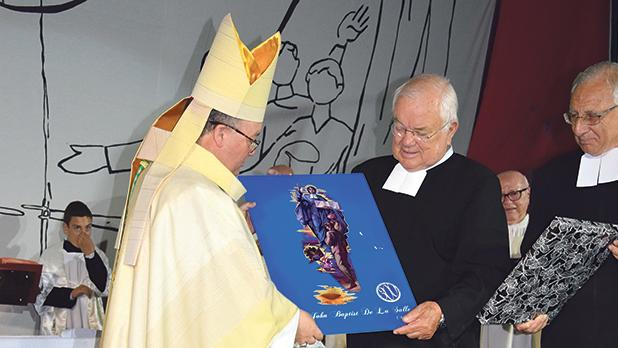 Archbishop Charles Scicluna being presented with a metal plaque by De La Salle college director Brother Martin Borg (centre). He was also presented with an etching of the saint by Stella Maris College director Brother David Mizzi (right).