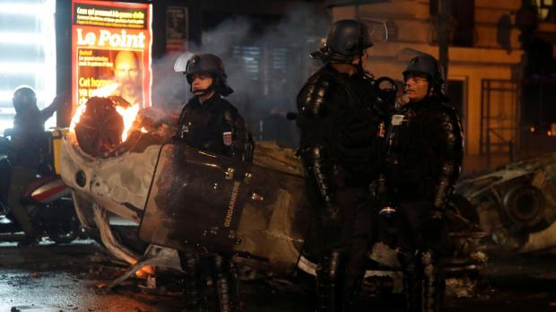 French riot police stand near an overturned burning car on avenue Kleber. Photo: Reuters