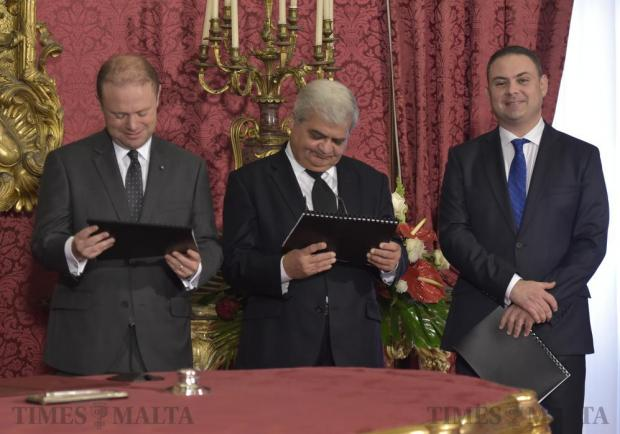 Prime Minister Joseph Muscat and Chief Justice Silvio Camilleri look at a booklet presented to them by the President of Malta whilst Justice Minister Owen Bonnici smiles at the cameras at the Palace in Valletta on November 21. Photo: Mark Zammit Cordina