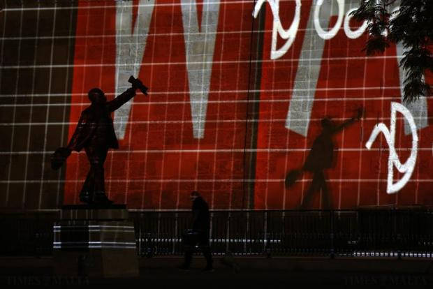 A technician (centre) walks past projections on the facade of St James Cavalier during a rehearsal of the opening ceremony of the 2015 Valletta Summit on Migration in Valletta on November 10. Photo: Darrin Zammit Lupi
