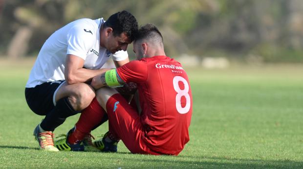 Hibernian's Clayton Failla (left) consoles Balzan's Paul Fenech after Balzan lost the match and the chance of being crowned Premier league champions during their Premier League match at the Hibernian's Stadium in Paola on April 21. Photo: Matthew Mirabelli