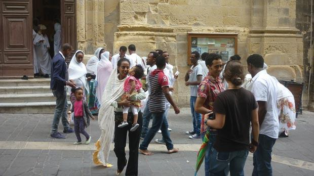 White-robed Eritrean Coptic Orthodox Christians emerging from the church of St James, on a Sunday morning.