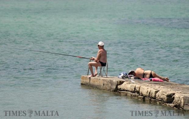 A man fishes while a woman sunbathes in Qawra on June 6. Photo: Chris Sant Fournier