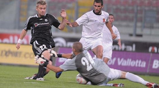 Valletta goalkeeper Andrew Hogg blocks Artmedia striker Sdynel Pospech as defender Josef Mifsud looks on.