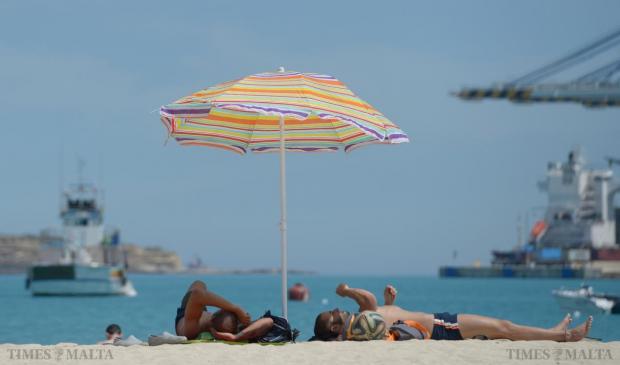 Two men enjoy the warm weather at Pretty Bay in Birzebbugia on May 3. Photo: Matthew Mirabelli