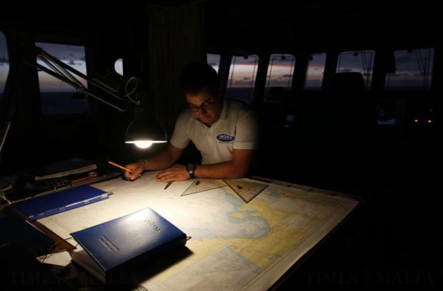 A crew member on the Migrant Offshore Aid Station (MOAS) ship Topaz Responder looks at navigation charts as the ship stands-by for migrants in distress in international waters off the coast of Libya on June 21. Photo: Darrin Zammit Lupi