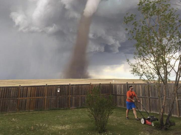 Canadian man mows lawn with tornado behind him