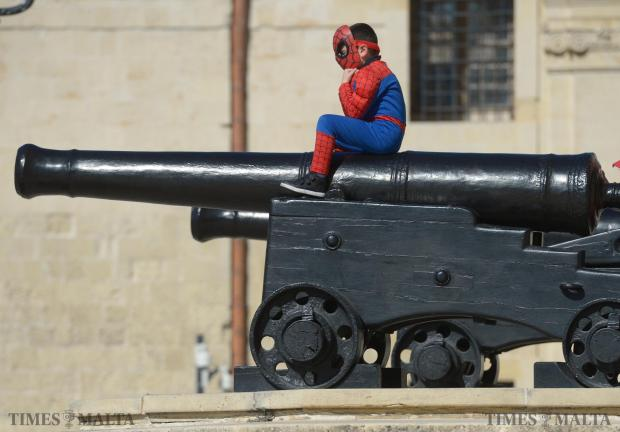 A boy dressed as Spiderman sits on the cannon at the entrance to Castille in Valletta on February 6. Photo: Matthew Mirabelli