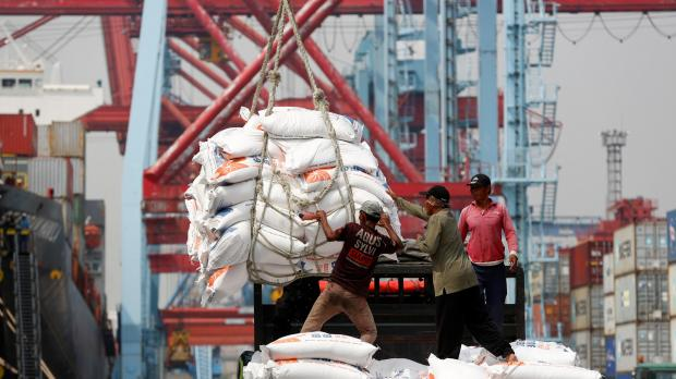Workers help unload bags of rice from a cargo ship on to a truck at Tanjung Priok Port in Jakarta, Indonesia