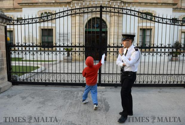 A young boy throws a paper airplane through the fence of the Police HQ during a protest organised by the Civil Society Network on November 5 in Floriana. The protestors called for the resignation of the Police Commissioner and the Attorney General. Photo: Matthew Mirabelli