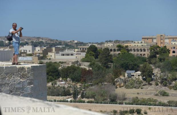 A tourist climbs on top of the bastions in Mdina to get a better viewpoint on August 16. Photo: Matthew Mirabelli