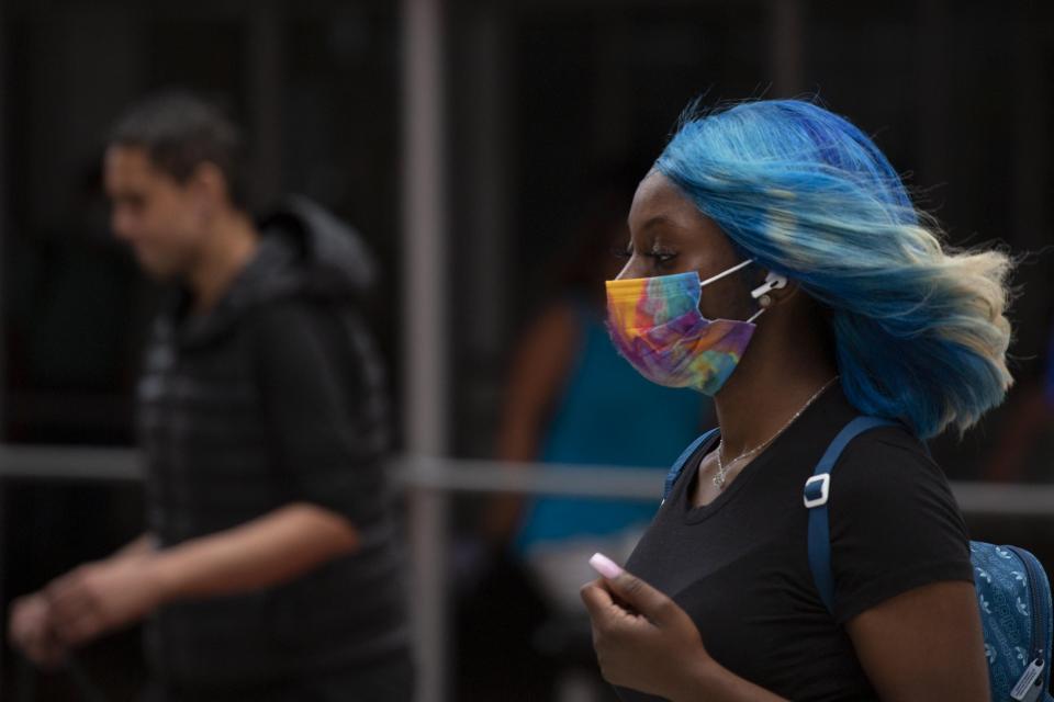 Una mujer lleva una máscara mientras camina por el centro de Manhattan, Ciudad de Nueva York.  Foto: AFP