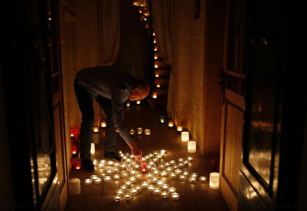 "A resident lights candles laid down in the form of a Maltese eight-pointed cross in the front hallway of his house during the activity ""Birgu by Candlelight"" in Vittoriosa on October 10. During the annual event, most street lights are switched off and the fortified city is lit up by candlelight, creating a magical ambience. Photo: Darrin Zammit Lupi"