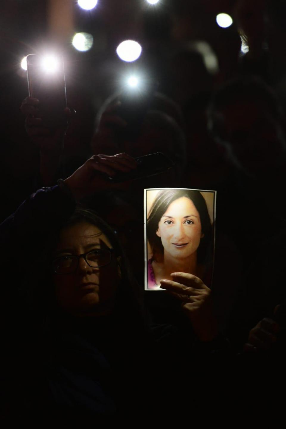 Daphne Caruana Galizia's sister holds up her portrait during a vigil held on Saturday November 16. Photo: Jonathan Borg