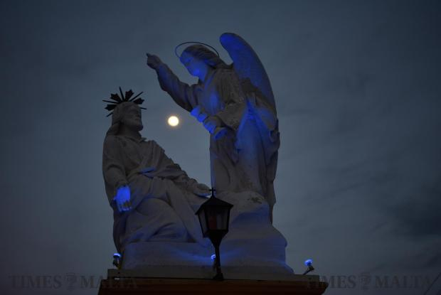 A full moon is caught between a statue during Maundy Thursday in Siggiewi on March 29. Photo: Mark Zammit Cordina