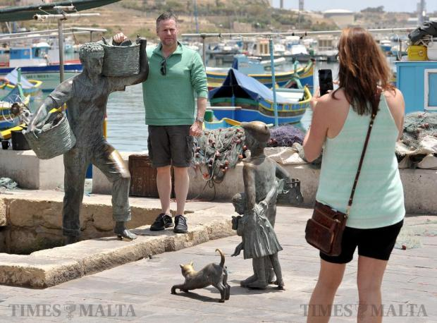 A tourist poses for a photograph by a statue of a fisherman at Marsaxlokk on May 25. Photo: Chris Sant Fournier