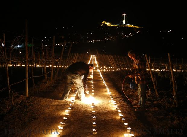 Volunteers light flaming torches to form a giant cross in a vineyard at the foot of the hill leading to Laferla Cross outside Siggiewi on March 24. Every year on Maundy Thursday, thousands of religious devotees make their way up the hill, the highest point on the Maltese islands, on a Seven Churches Visitation pilgrimage as part of Holy Week activities before Easter. Photo: Darrin Zammit Lupi
