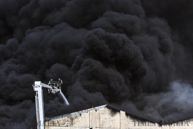 Firefighters try to tame a blaze that engulfed a recycling factory in Ħal Far. The thick black smoke was visible from distant localities in Malta. Members of the Armed Forces of Malta assisted the Civil Protection Department in controlling the fire on 28 April. Photo : Jonathan Borg