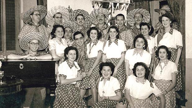 The Coons, 1951. Front row (from left) (1) Josephine Azzopardi (Mrs Charlie Sammut), (2) Cora Agius Ferrante (Mrs Arthur P Camilleri), (3) Mollie Debono (Mrs Freddie Zammit Tabona). Middle row: (1) Leslie Grech, (4) Bertie Mizzi, (5) Elda Radmilli (Mrs Bertie Mizzi), (6) Mafine Xuereb (Mrs Leslie Grech), (7) Yvonne Sullivan (Mrs Tony Amadeo), (8) Lola Mizzi (Mrs George Sammut), (9) Iris Radmilli (Mrs George Sciortino). Back row: (4) Tony Amadeo. Photo: The Royal Studio, Valletta