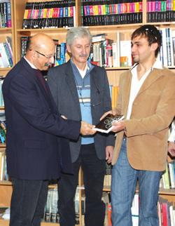 Steven Camilleri (right) presenting the novel to Marcel Xuereb. Also seen is Pierre Buttigieg (centre).