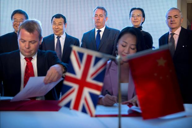 British Secretary of State for International Trade Liam Fox watches the signing ceremony for memorandums of understanding between British and Chinese firms and institutions at the British Ambassador's Residence in Beijing.