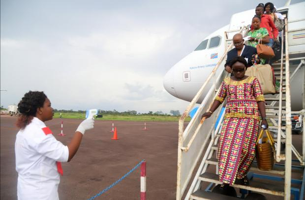A Congolese health worker checks the temperature of passengers disembarking from a Congo Airways plane in Mbandaka.
