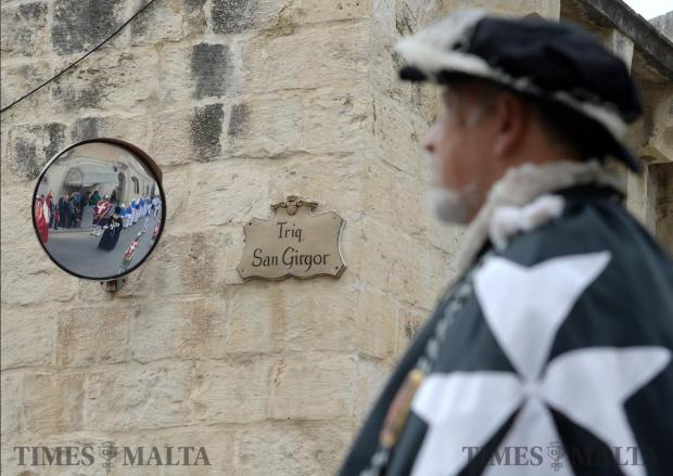 A man dressed up as a Grand Master passes a street sign during the procession of San Girgor in Zejtun on April 4. Photo: Matthew Mirabelli