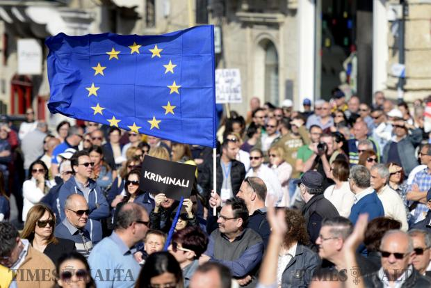 A placard with 'Krimianli' Criminals is lifted whilst the European Union Flag waves over a crowd gathered for an anti-corruption protest in Valletta on April 23. Photo: Mark Zammit Cordina