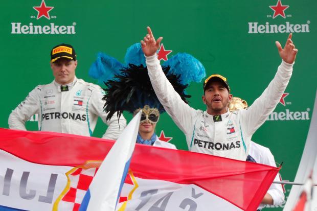 Mercedes' Lewis Hamilton celebrates on the podium after winning the race as teammate Valtteri Bottas looks on.