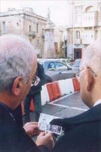 Resources and Infrastructure Minister Ninu Zammit, holding a postcard, shows Ray Bondin, president and coordinator of the Cottonera Rehabilitation Committee, where the clock tower used to stand.