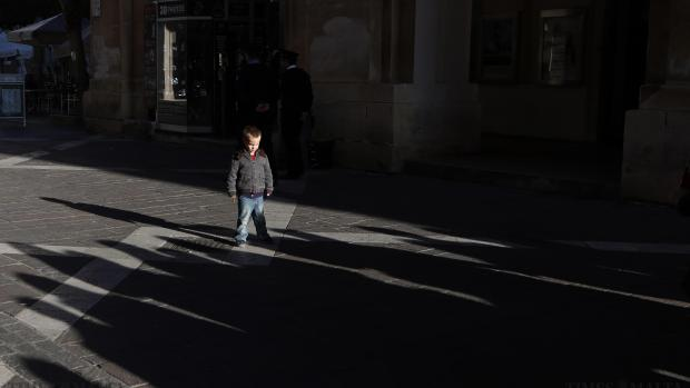 A boy stands in the middle of the street as people walk towards him during a silent protest and tribute to the victims of the shootings by gunmen at the offices of the satirical weekly newspaper Charlie Hebdo in Paris, in Valletta on January 11. Photo: Darrin Zammit Lupi