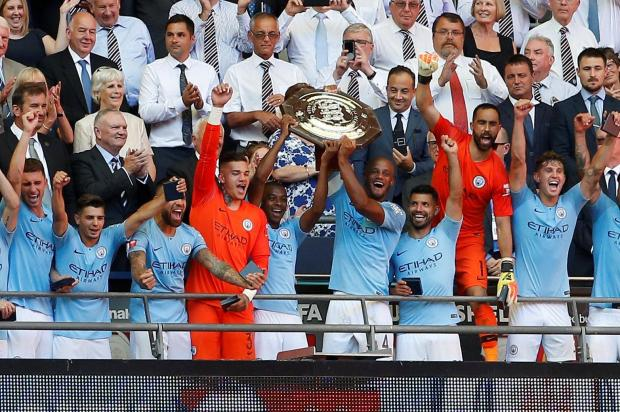 Manchester City players lift the Community Shield at Wembley Stadium.