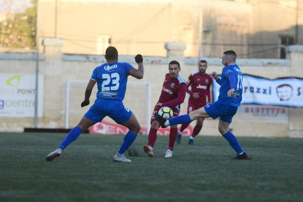 Gżira United midfielder Roderick Briffa (centre) hits a pass despite the challenge of Daren Falzon. Photo: Jonathan Borg