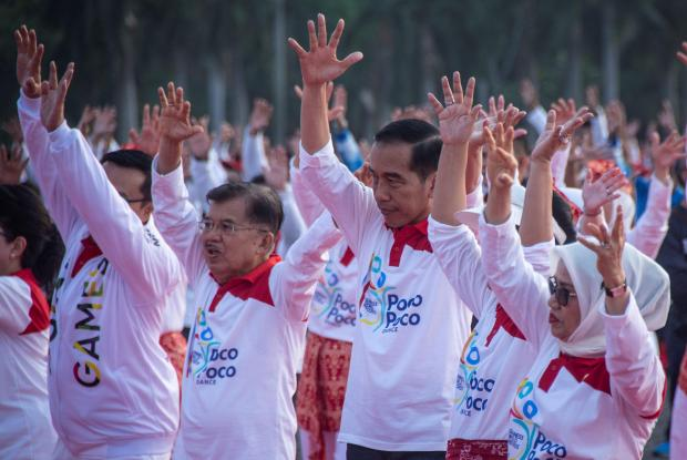 Indonesia President Joko Widodo stands beside Vice President Yusuf Kalla during a dance called 'poco-poco' at the National Monument in Jakarta.